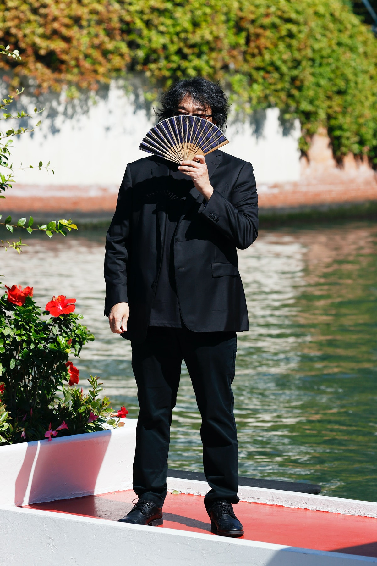 Bong Joon-ho holding a fan in front of his face