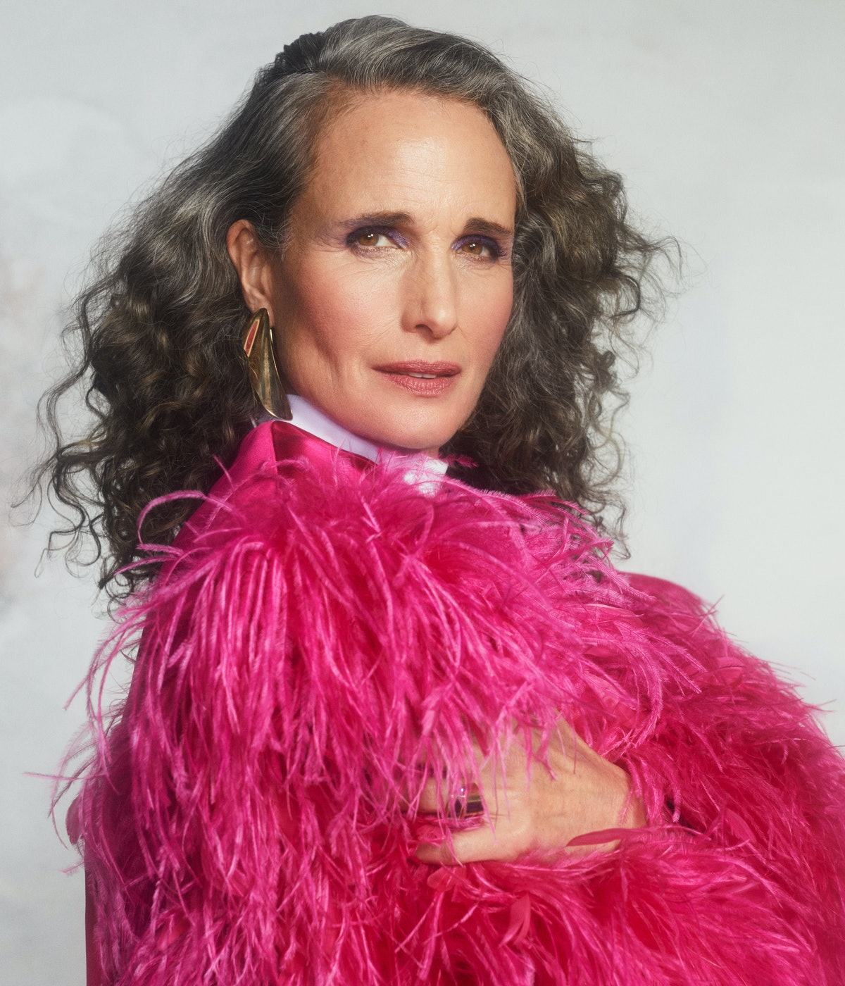 A portrait shot of TZR cover star Andie MacDowell sporting gray hair and a pink feathered Gucci top.