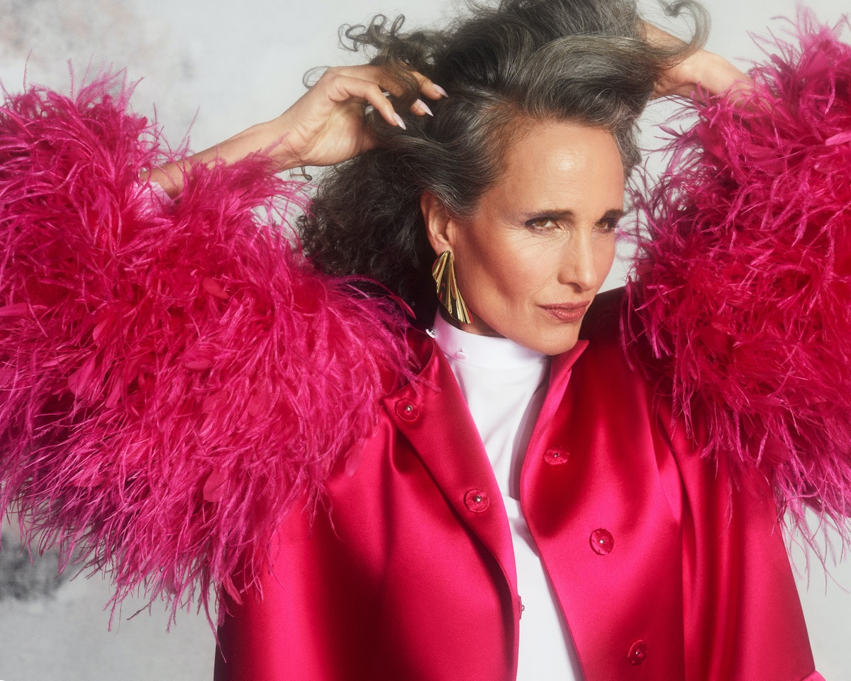 TZR cover star Andie MacDowell poses with her hands in her hair while wearing a pink feathered Gucci...