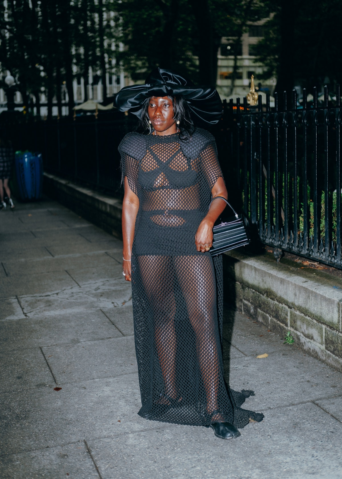 The woman is wearing a mesh dress with a large hat.