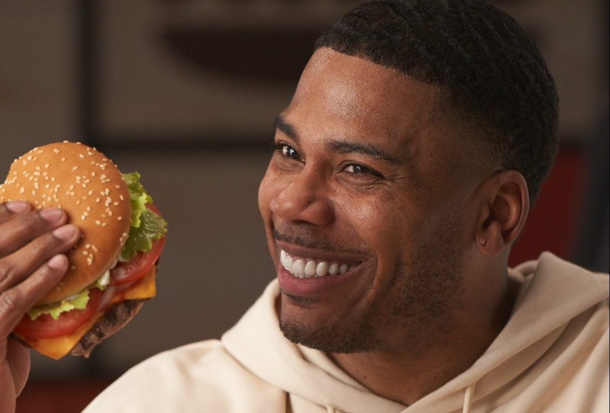 Nelly holding a burger in his hands.