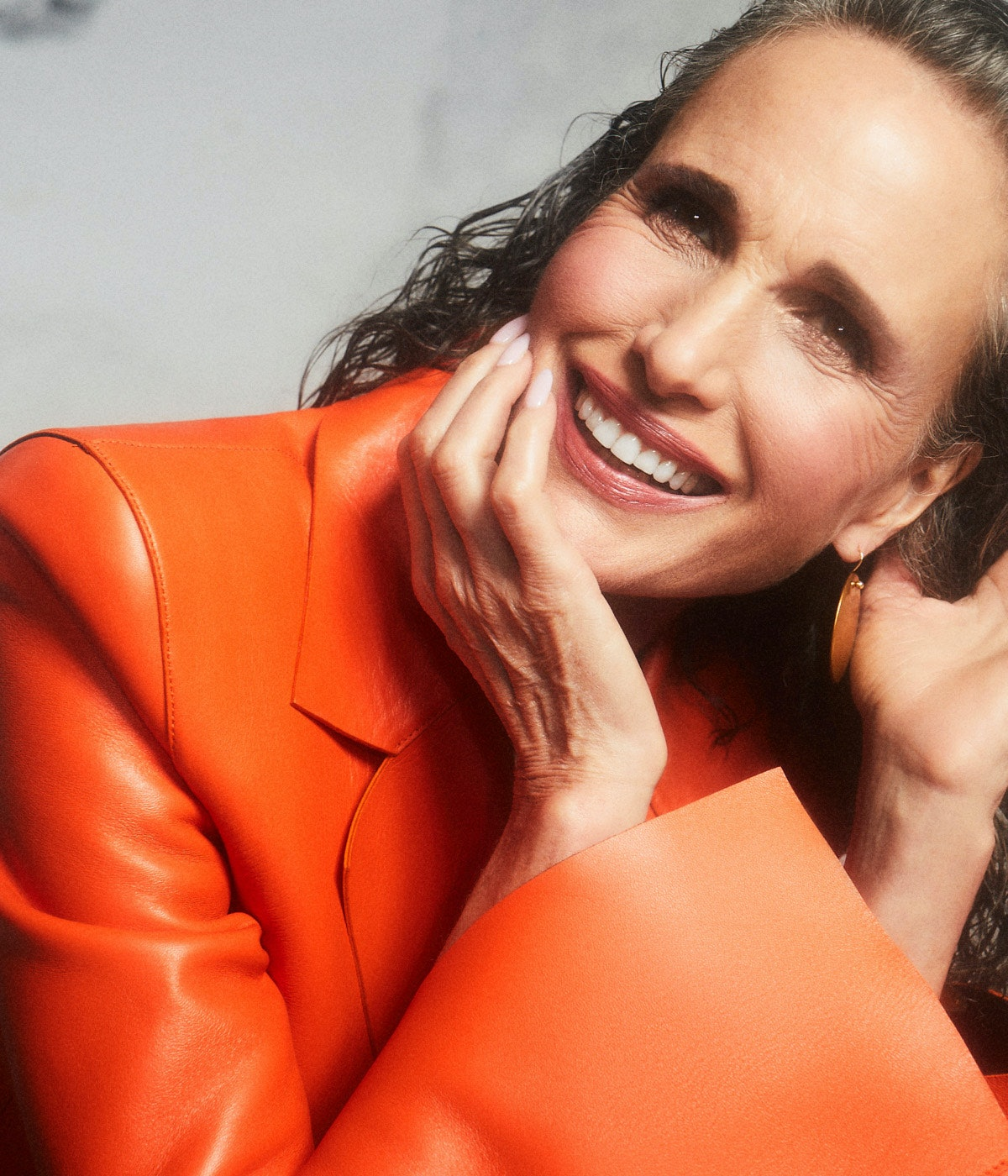 A portrait shot of TZR cover star Andie MacDowell with gray hair wearing an orange Off-White c/o Vir...