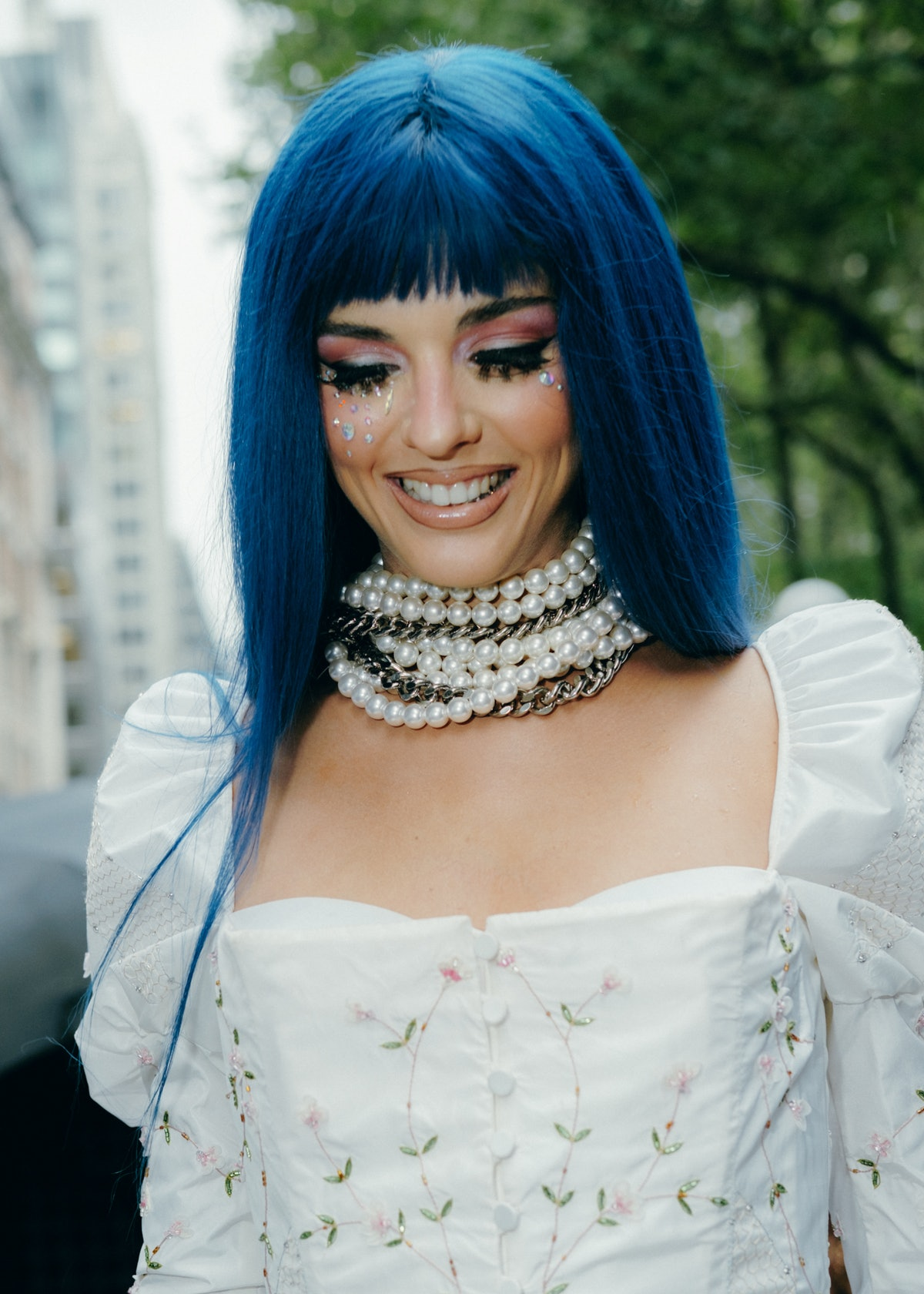 The woman wears blue hair and a lot of pearl necklaces.