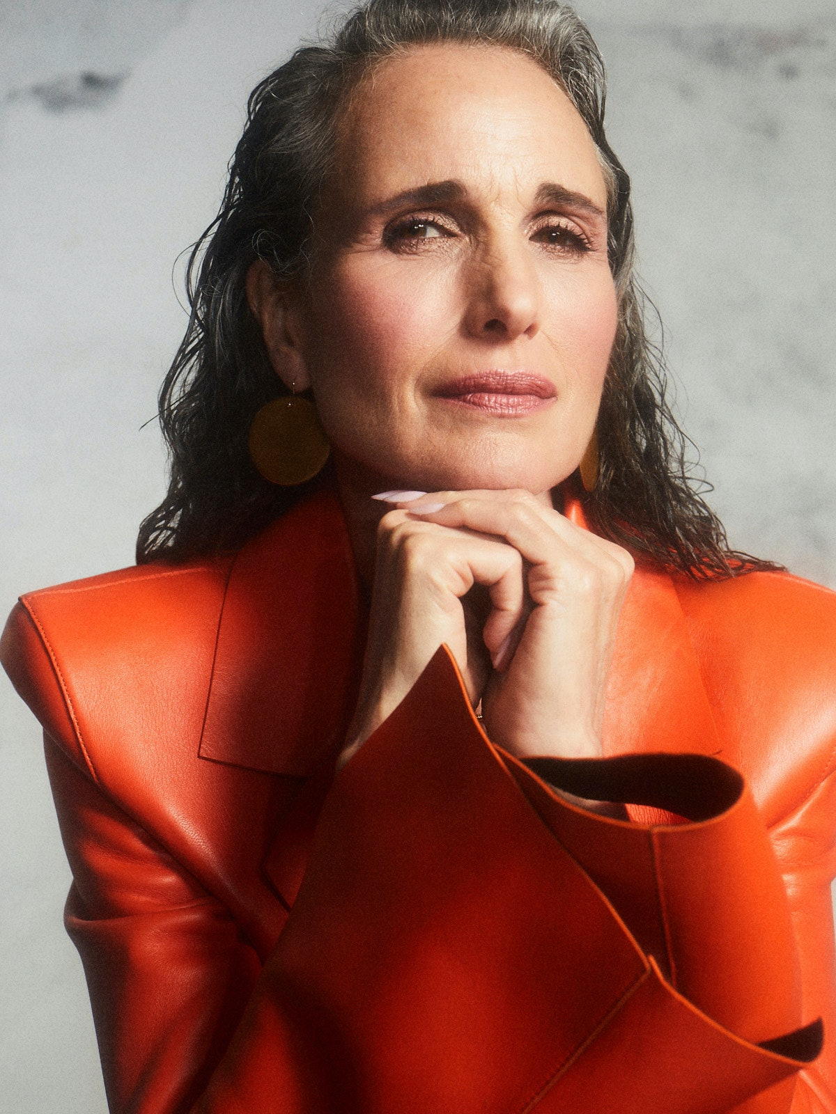 A close-up image of TZR cover star Andie MacDowell with her hands beneath her chin wearing an Off-Wh...