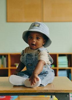 baby wearing osh kosh b'gosh overalls and hat
