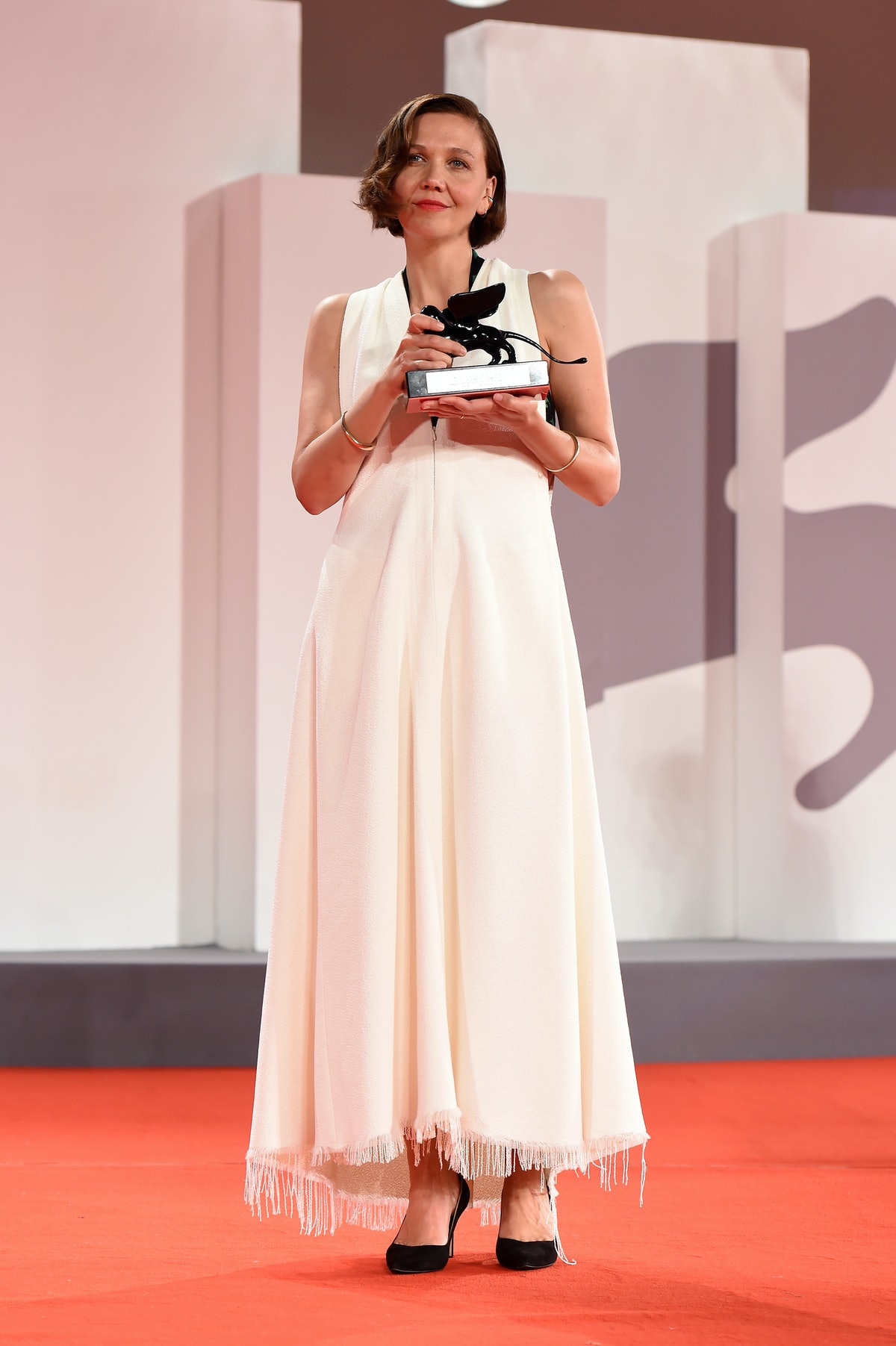 """Maggie Gyllenhaal receives the Award for Best Screenplay for """"The Lost Daughter"""" during the closing ..."""
