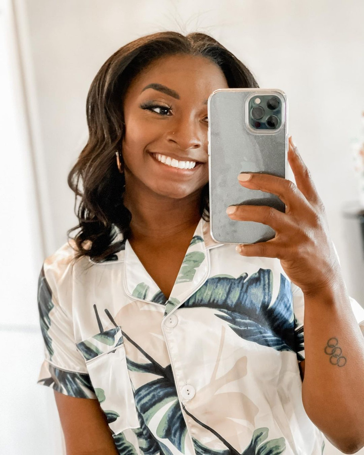 Simone Biles with curled hair taking mirror selfie and smiling
