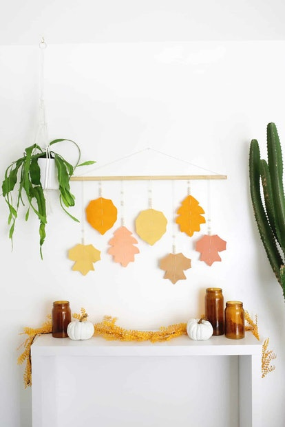 Felt leaves in orange pink and yellow hanging from wooden dowel
