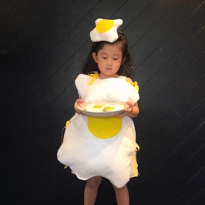 Little girl dressed up as fried egg