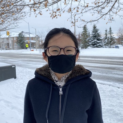 child outside in snow wearing a black kids face mask from Threads