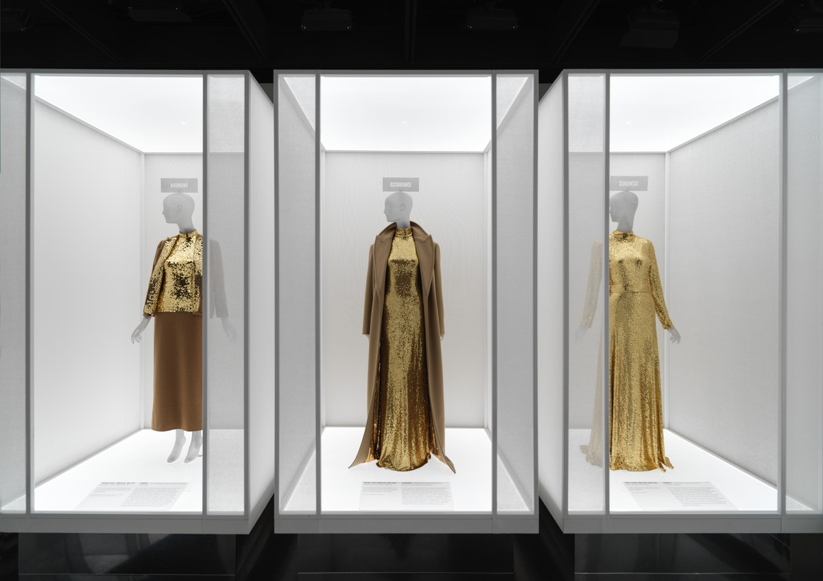 Three gold sequinned outfits in museum display cases.