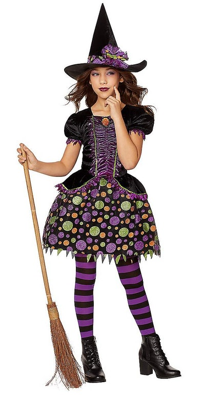 Young girl posing in witch Halloween costume
