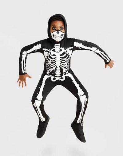 Boy jumping, wearing skeleton costume