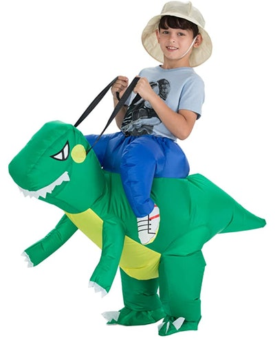 Little boy wearing a costume that makes it look like he's riding a dinosaur