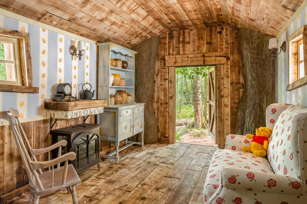 Disney's 'Winnie the Pooh' treehouse Airbnb has Winnie the Pooh details inside like hunny pots and w...