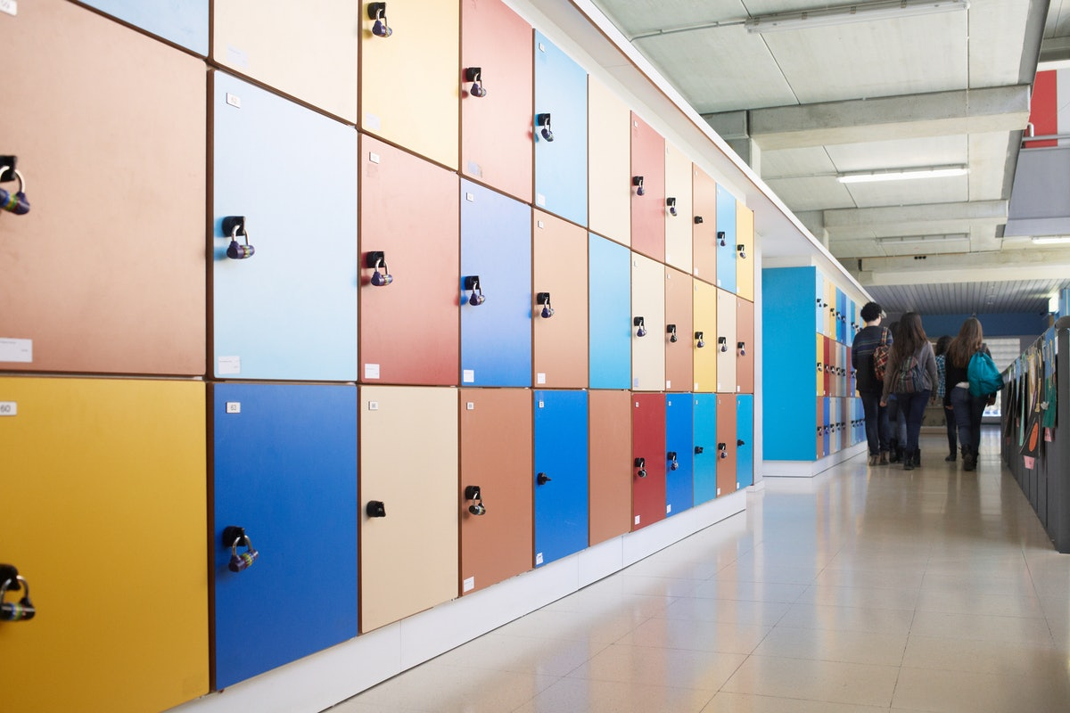Students seen at the end of a long hallway lined with lockers