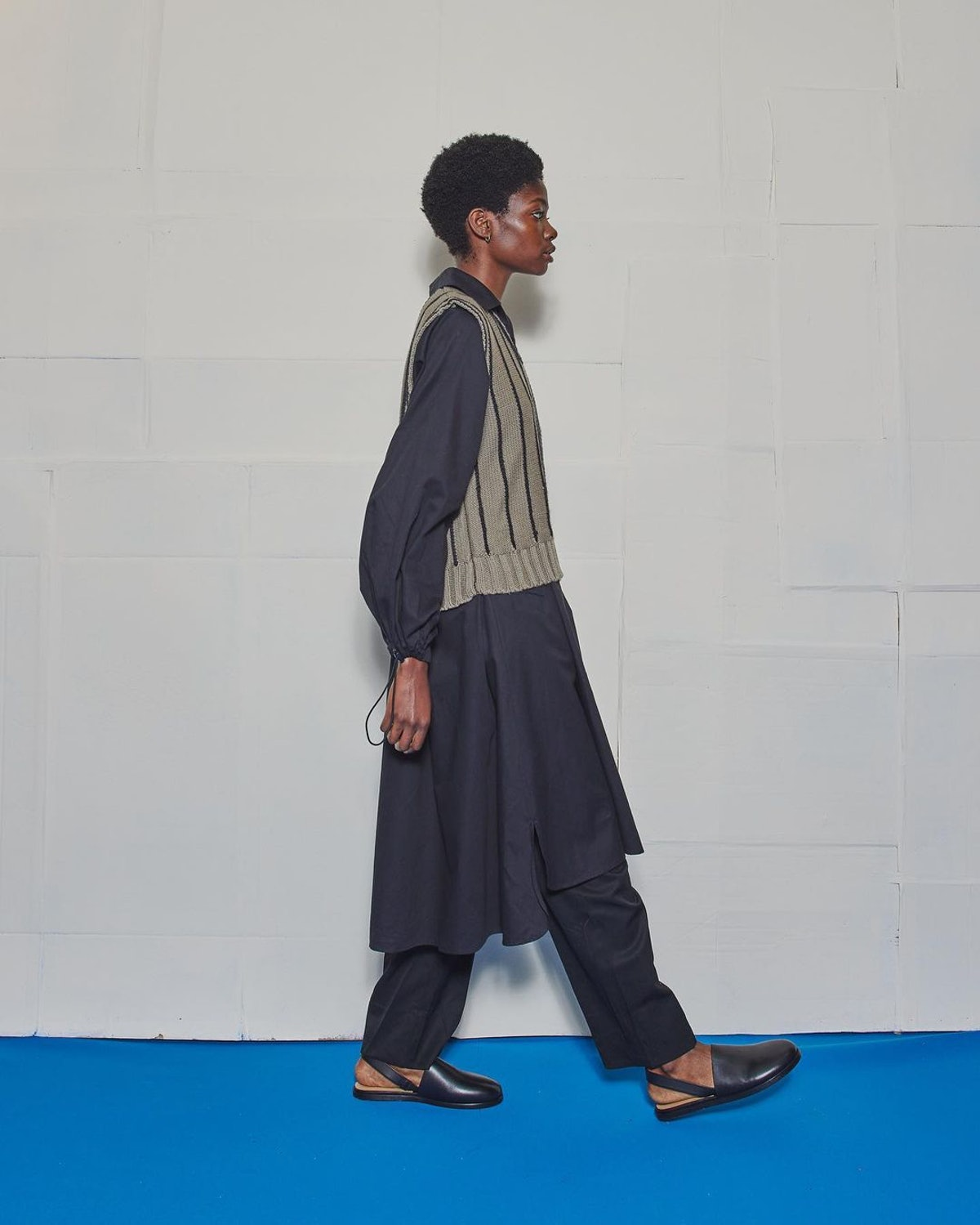 Model in vest and dress with sandals