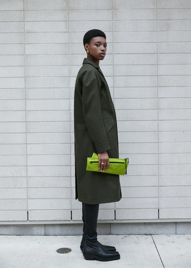 Model in green coat holding green clutch
