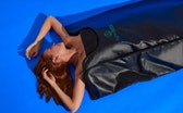 Woman with arms out laying inside Higher Dose Sauna Bag