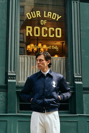model standing in front of restaurant with blue jacket and white pants