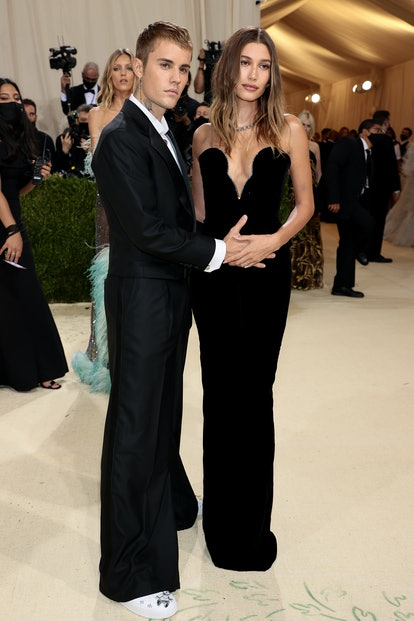 Justin Bieber puts his hand on Hailey Baldwin's stomach as they attend The 2021 Met Gala Celebrating...