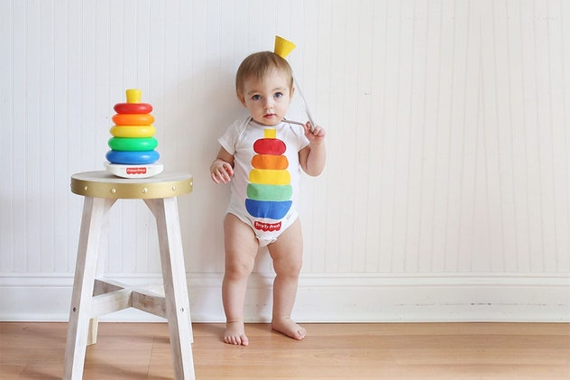 A baby wearing a onesie painted to look like a Fisher Price stacking toy