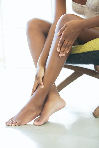 Woman applying tanning cream to legs