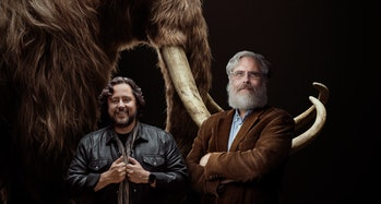 Ben Lamm and George Church of Colossal posing in front of a mammoth