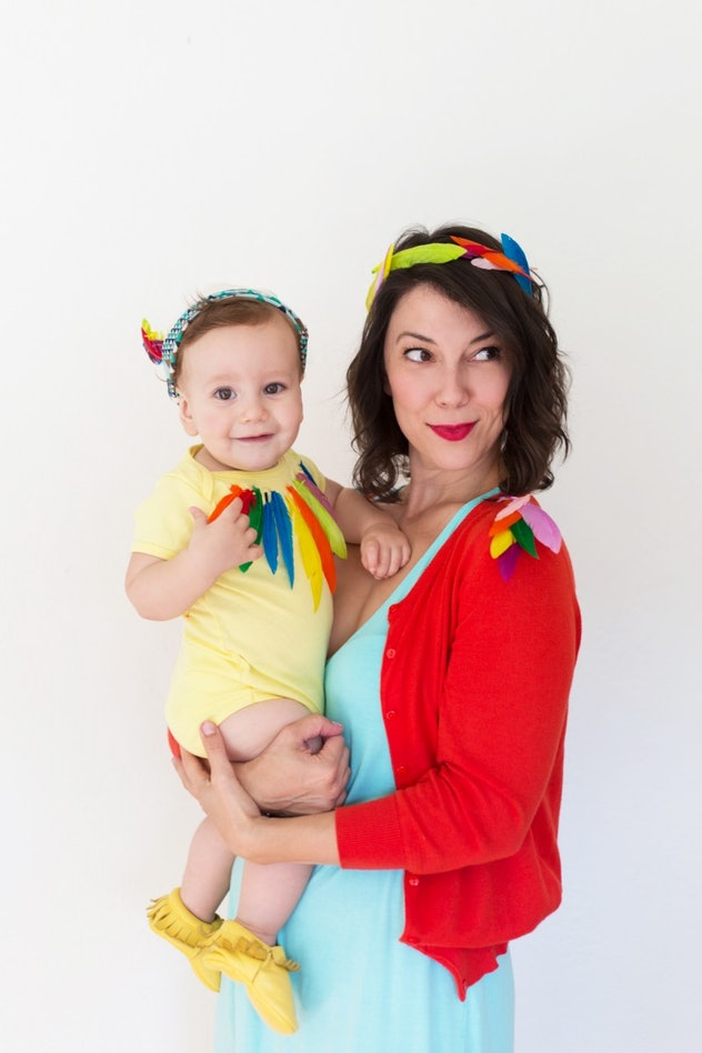 Mom and baby wearing brightly colored clothes with colorful feathers