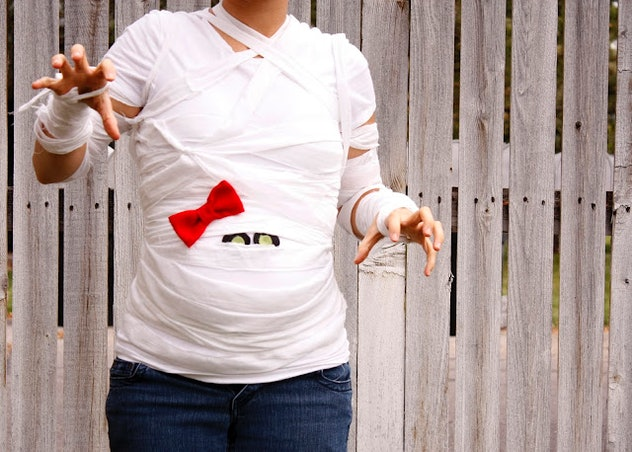 Pregnant woman in costume that looks like the bump is a mummy