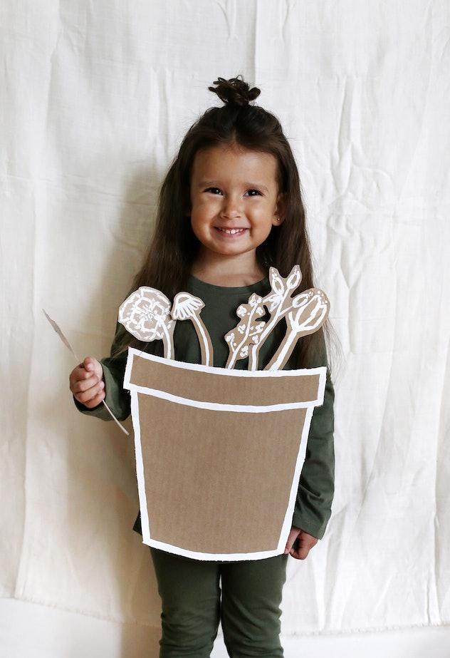 Little girl in green, wearing flower pot made from cardboard