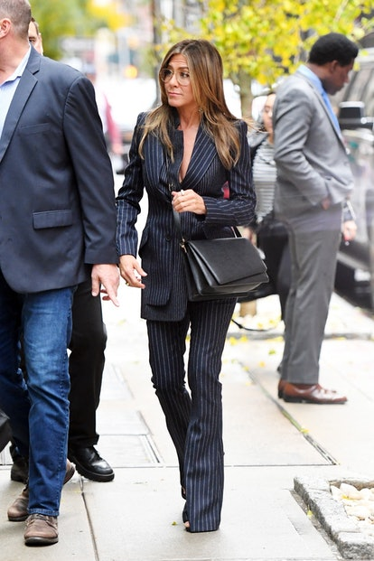 Jennifer Aniston wears black Valextra Twist shoulder bag and pinstripe pantsuit while out in SoHo, N...