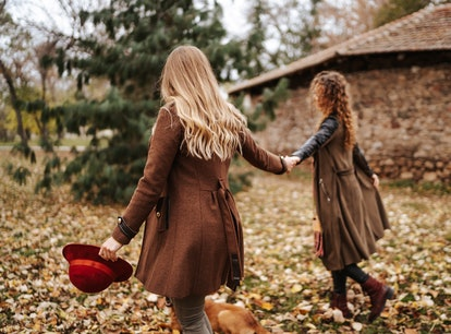 Young couple holding hands while walking through leaves in fall 2021, the most romantic season for t...