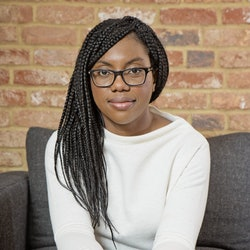 Kemi Badenoch sat on a grey sofa wearing a white jumper and blue smart trousers. Her hair is in brai...