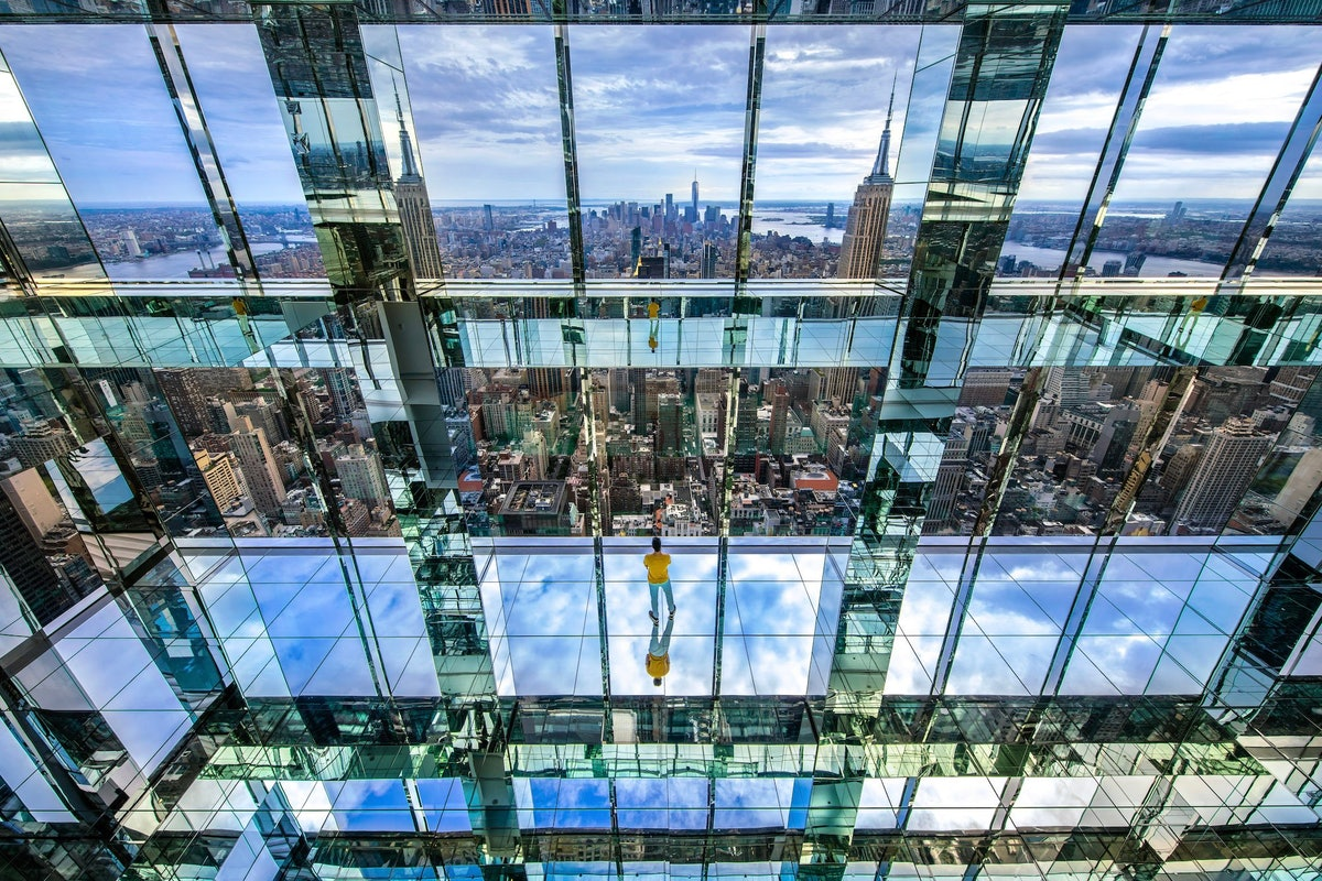 Glass, reflective, mirrored room overlooking the NYC cityscape.