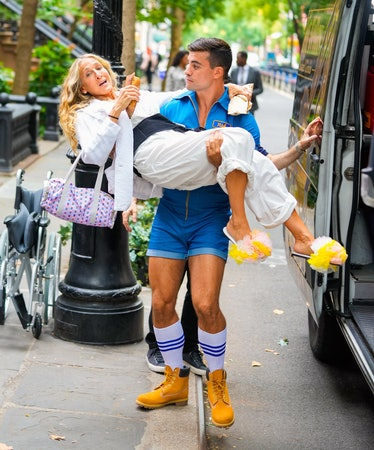 Carrie Bradshaw in hunk's arm.
