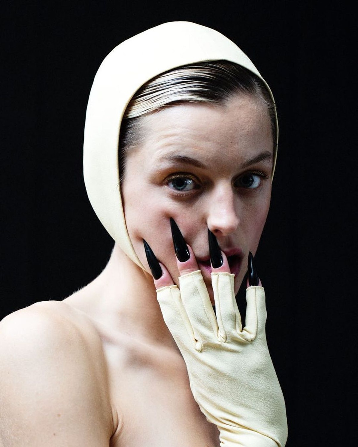 Emma Corrin showing off their talon nails at the 2021 Emmys