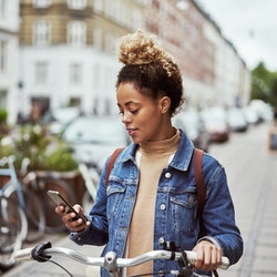 Woman standing with her bike looking at her phone.