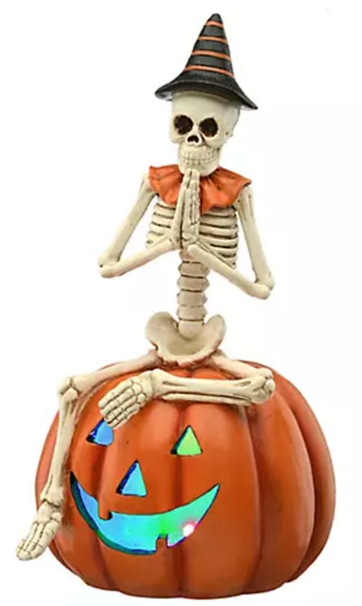 This Halloween tabletop decor from BJ's features a skeleton sitting on a pumpkin.