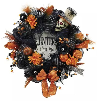 A wreath decorated for Halloween in skulls and leaves