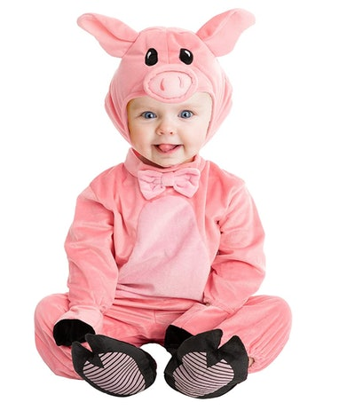 Baby sitting up in a pig costume