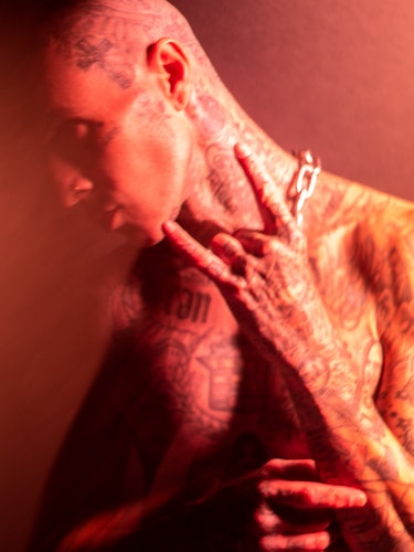 A side-profile image of Travis Barker in front of a red backdrop.