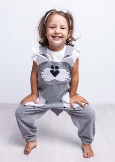 Child wearing a pair of cat overalls