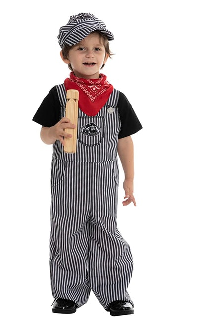 Toddler in overalls, hat, and scarf to look like a train conductor
