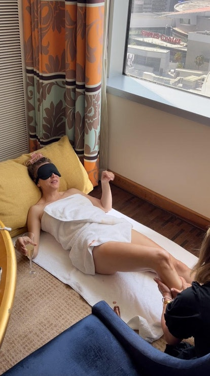 Kaley Cuoco wearing face mask and drinking champagne