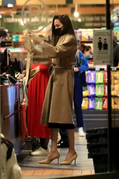 Angelina Jolie wears a trench coat, black dress, and nude heels when grocery shopping.