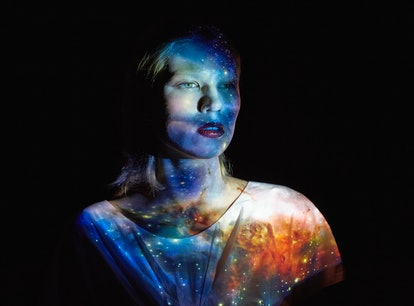 Young woman with the universe projected on to her to show the Grand Cross in astrology.