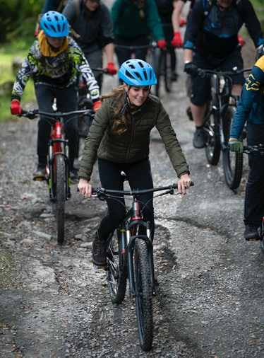 Catherine, Duchess of Cambridge rides a mountain bike during a visit to the Windermere Adventure Tra...