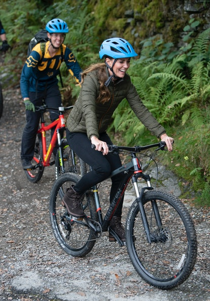 Catherine, Duchess of Cambridge rides a mountain bike during a visit to the Windermere Adventure Tr...