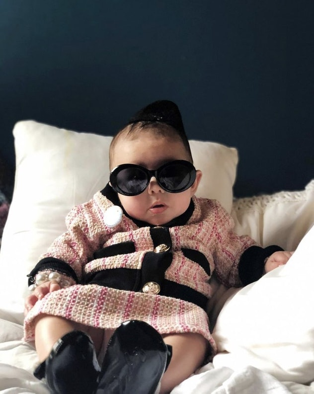 baby dressed as Jackie Onassis Kennedy for Halloween in pink plaid suit and black sunglasses